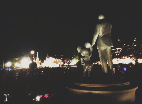Walt Statue looking of Main Street USA at night